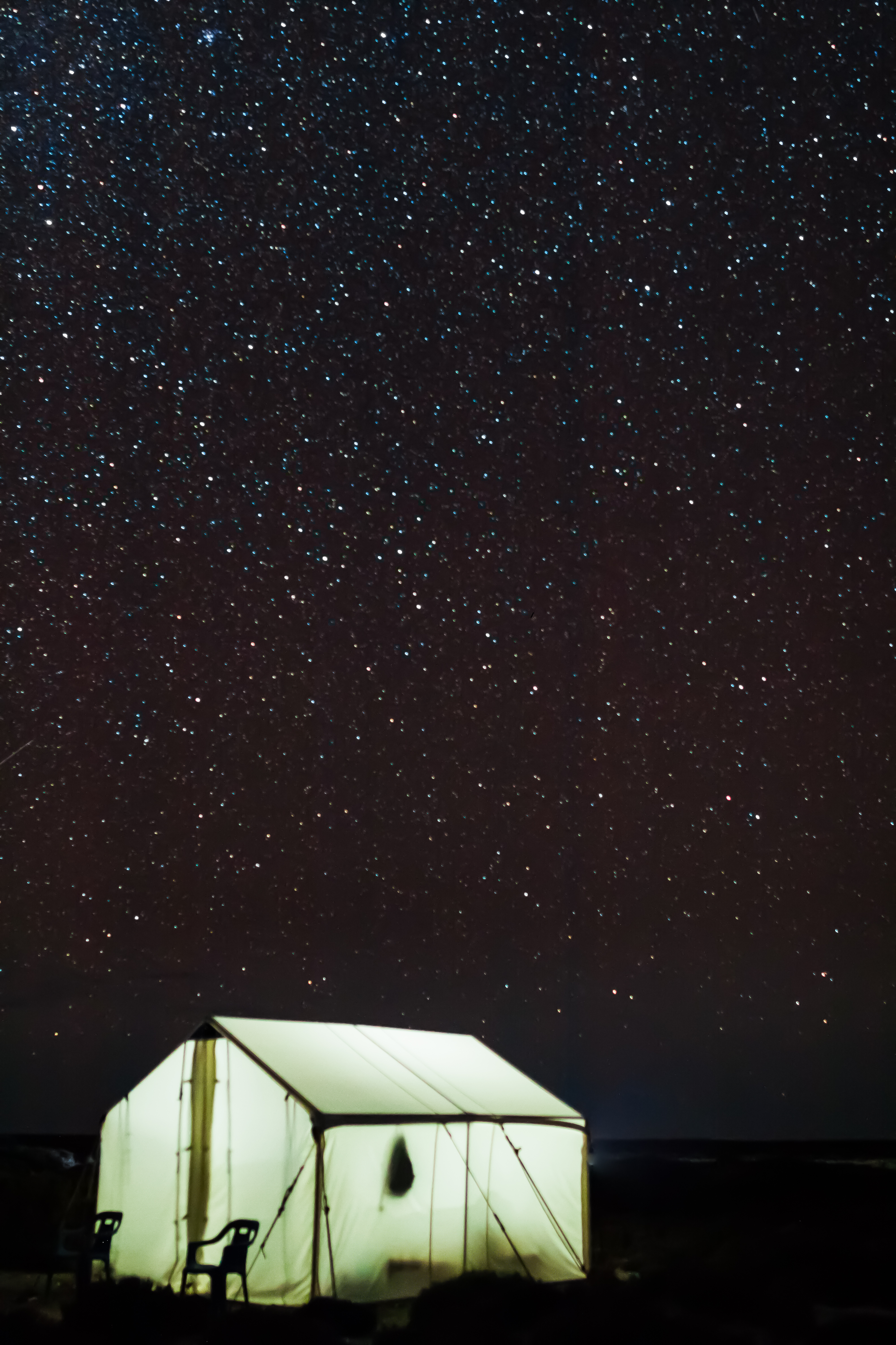 Illuminated tent at night with stars above