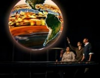 People watching a large globe of the earth