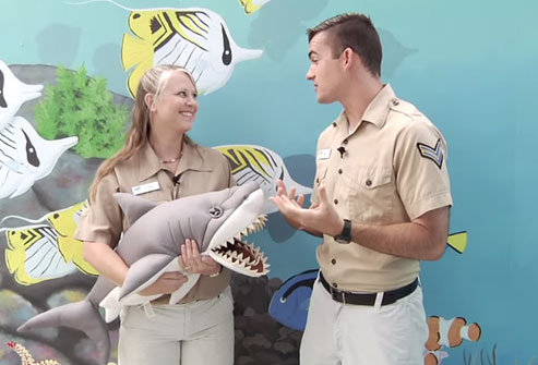 Two educators holding a shark stuffed animal
