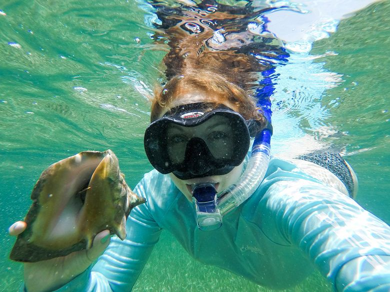 woman snorkeling underwater holding conch shell - popup