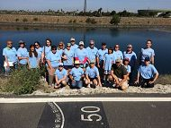 Group of people in blue shirts standing in front of a river links to Southern California Sea Turtle Monitoring Project