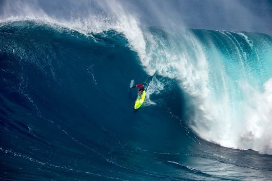 Big wave surfer Jamie Mitchell rides a surfboard down the face of a cresting wave - popup