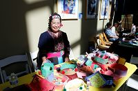 Smiling woman poses with paper hat craft - thumbnail
