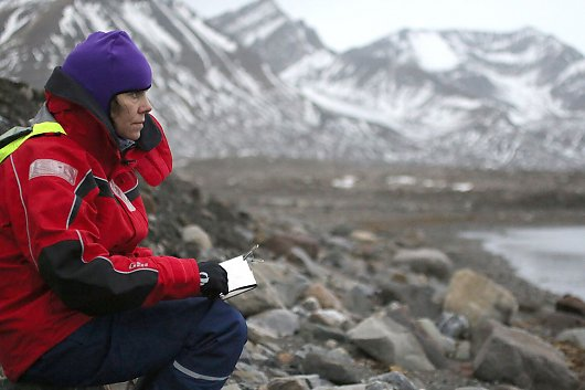 Woman wearing cold-weather clothes looks out on rocky shore