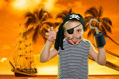 Boy dressed as a pirate for Halloween in front of tropical background