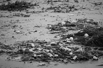 Black and white photo of trash floating on ocean