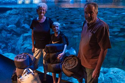 Family with sleeping bags in front of otter exhibit