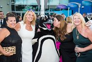 Group of well dressed people posing with Penguin costumed character links to Contact