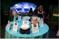 Round table with descriptive signs of silent auction items links to Register to Bid