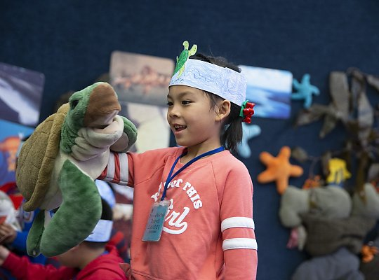 girl with a hat on playing with a turtle puppet - slideshow