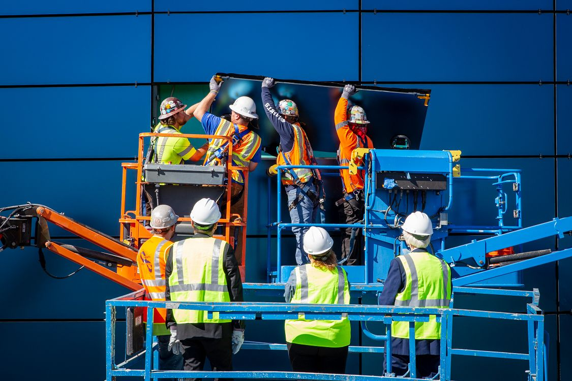 Crew on a lift installs glass panel in Pacific Visions facade while officials watch - lightbox