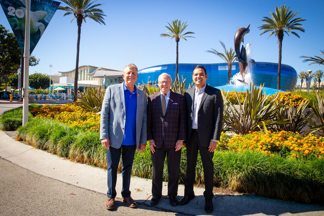 Frank Colonna, Jerry Schubel, and Mayor Robert Garcia stand in front of the Aquarium with the Pacific Visions wing in the background. - lightbox