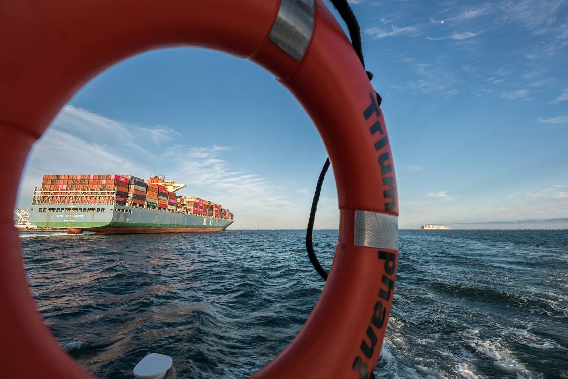 Photograph pf a container ship on the ocean viewed through rescue ring buoy labeled Triumphant - lightbox