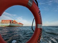 Photograph pf a container ship on the ocean viewed through rescue ring buoy labeled Triumphant