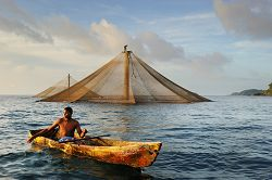 A young man in a canoe fishes near a fish farm at sunset.