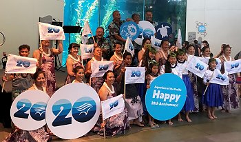 2018 Pacific Islander Festival participants with 20th Anniversary signs and flags