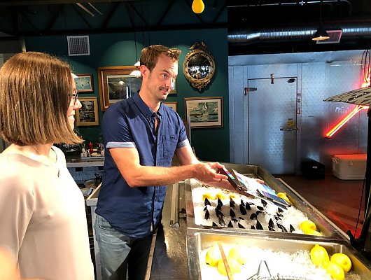Chef Barton Seaver and Halley Froehlich stand behind a seafood counter full of mussels to demonstrate how to source them.