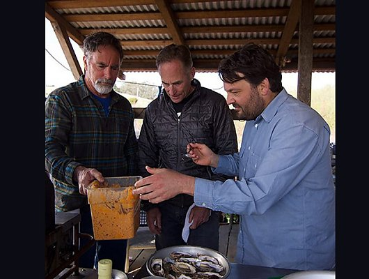Chef Stuart Brioza and farmers Terry Sawyer and John Finger apply butter recipe to oysters before they grill them. 900x600 gallery.