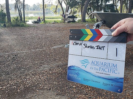 Clapboard with Aquarium and Seafood for the Future logos in foreground with South Carolina wetlands and farmer on boat in background. 900x600 gallery - slideshow