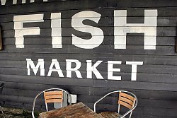 Fish Market sign on the side of a wooden building - popup