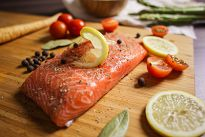 Preparing a salmon steak with lemon, peppers, and capers