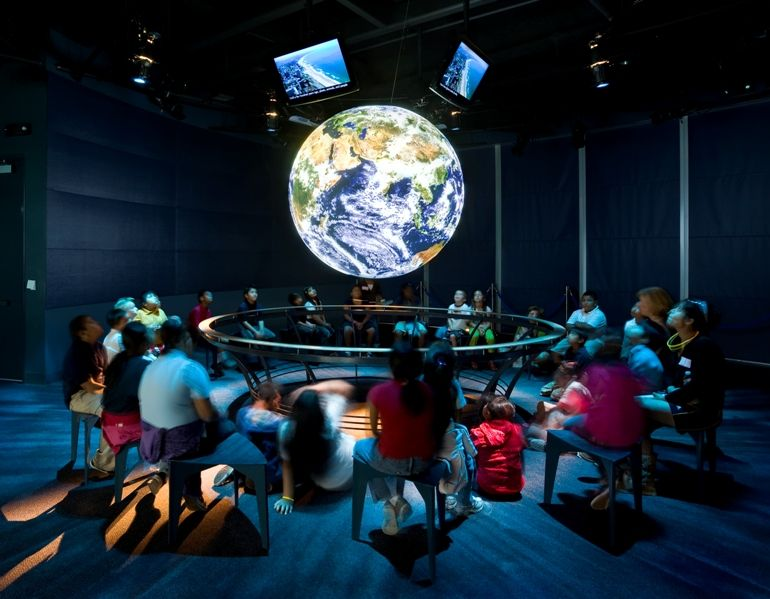 Guests surround globe Science on a Sphere - lightbox
