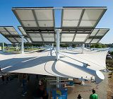 Solar panels above an exhibit links to Reducing Our Carbon Footprint