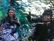 Divers in water giving thumbs up