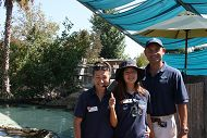 Teenager girl gives thumbs-up flanked by parents in Shark Lagoon.