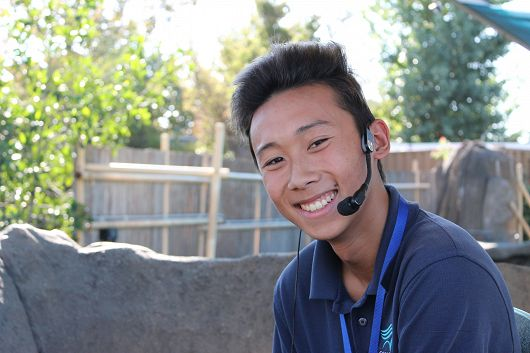 Young male volunteer smiling with a microphone - popup
