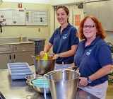 adult volunteers with feed buckets for animals