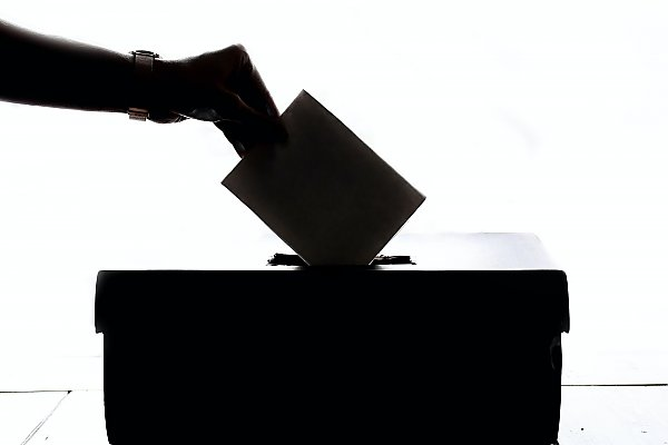 silhouette of a hand submits a ballot in a box