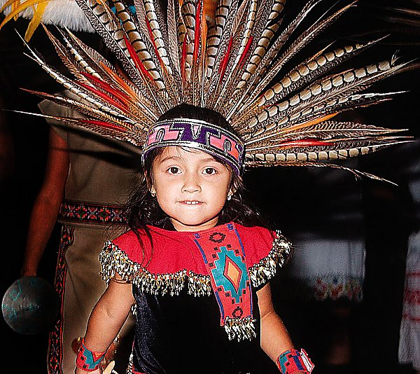 Child wearing traditional Aztec headdress and outfit