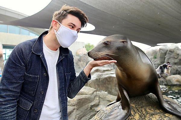 Masked young man poses with a sea lion