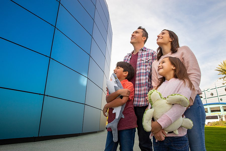 Family of four looks looking at Pacific Visions exterior