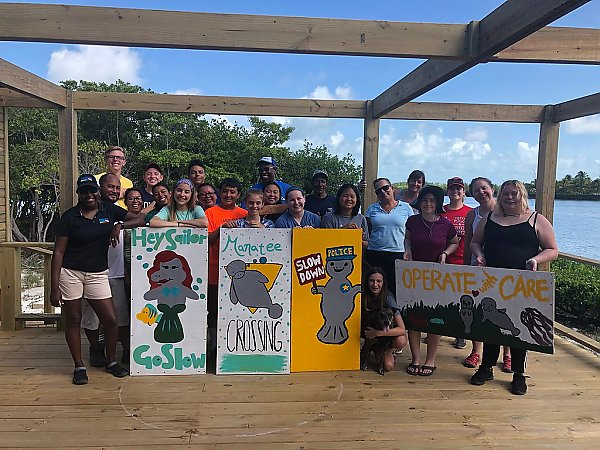 Students pose on doc with manatee signs