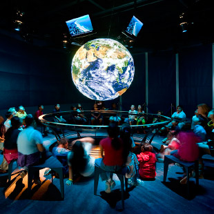 People in room looking at globe with earth projections