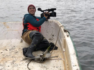 Camera operator Bailey Galvin-Scott is dressed in wadders on a boat, ready to get some images from the Hog Island Oyster Farm.