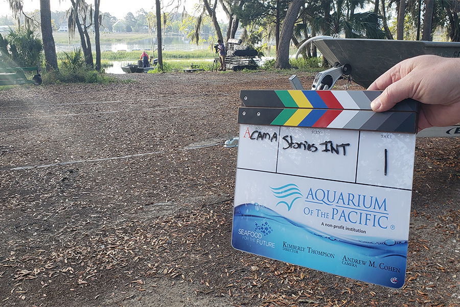 Clapboard with Aquarium and Seafood for the Future logos in foreground with South Carolina wetlands and farmer on boat in background. 900x600 gallery