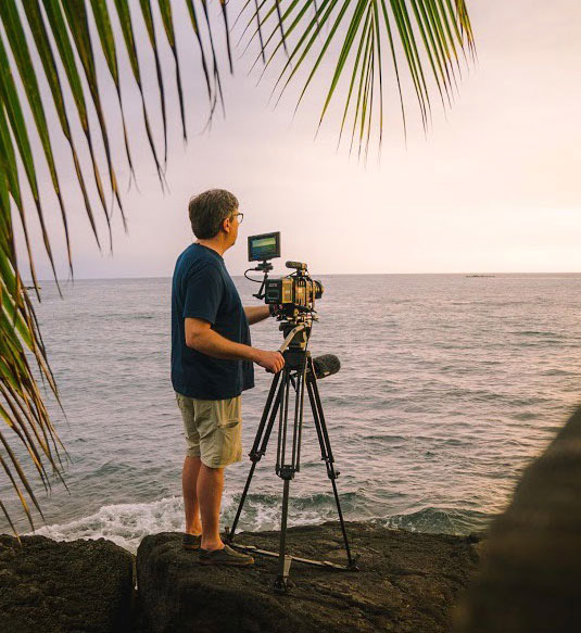 Andrew Cohen films Hawaii sunset with palm fronds in foreground.