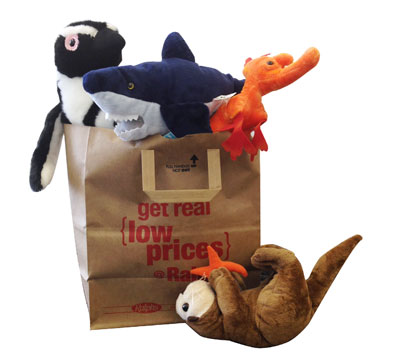 Stuffed penguin, shark, and sea dragon plushes in a Ralphs paper bag with a stuffed sea otter plush in front of it.
