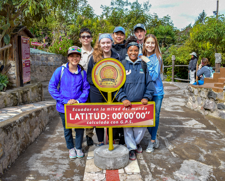 Seven students pose near a sign marking the equator