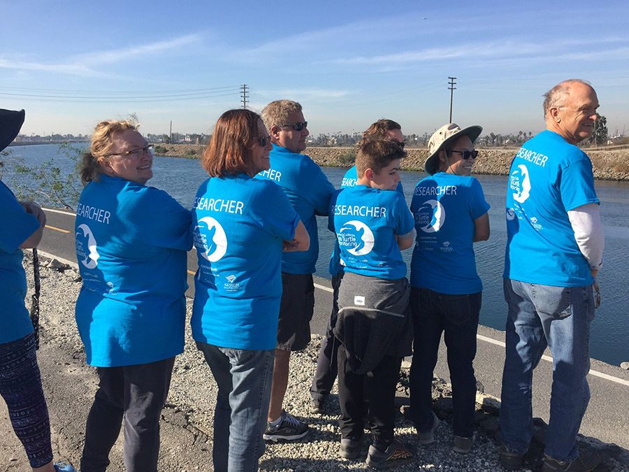 Several volunteers in blue shirts looking at the river
